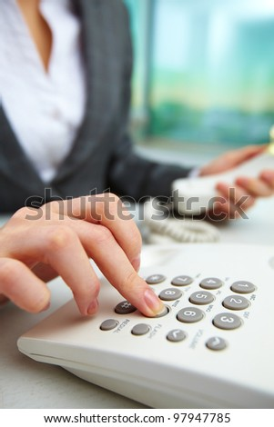 Female hand dialing telephone number - stock photo