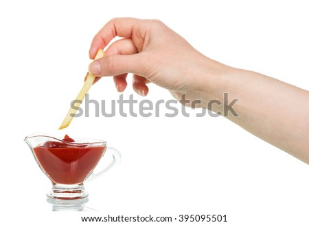 Female hand down french fries with ketchup in a cup isolated on white background. - stock photo
