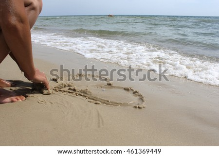 Female hand draw on the sand near the sea heart.