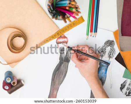 female hand drawing fashion sketch on desk with designing equipment - stock photo