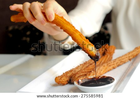 Female hand enjoy dipping Churros to dark chocolate sauce - stock photo