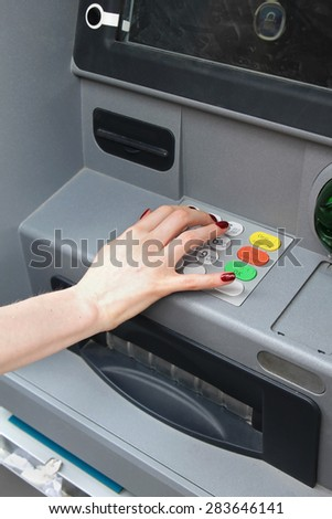 Female hand entering pin code on atm machine