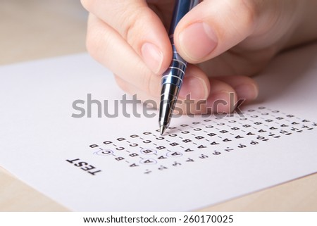female hand filling test score sheet with metal pen - stock photo
