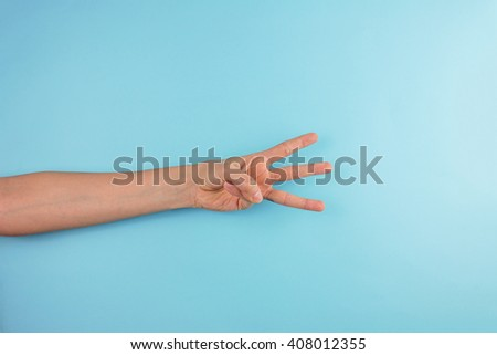 Female Hand Gesturing on Blue Background. - stock photo