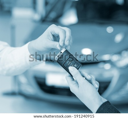 Female hand getting modern car key on a car background - stock photo