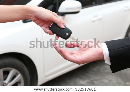 Female hand giving a key for buyer or rental car. - stock photo