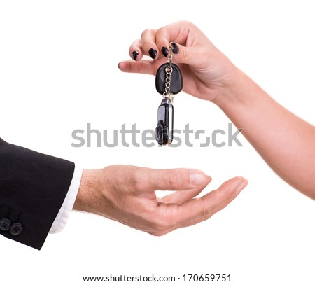 Female hand giving car key to male hand on a white background