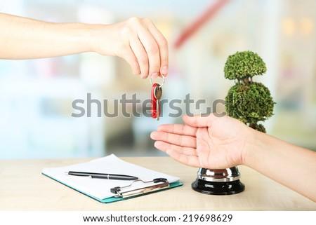 Female hand giving hotel key on reception desk, on bright background - stock photo