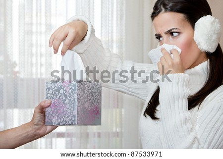 Female hand giving to young teenage girl another handkerchief from the box while she blowing her nose. Focus on the hand. - stock photo