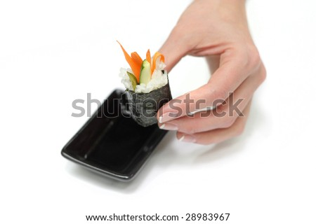 Female hand hold a Japan sushi and dip it in the soy sauce