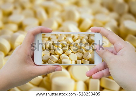 Female hand hold mobile smart phone taking photo of yellow medicine pills