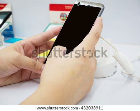 female hand hold mobile smartphone in shop