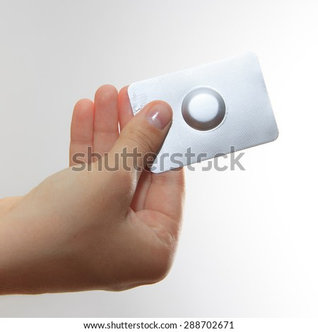 Female hand hold one medical pill in blister pack against white background, view 1