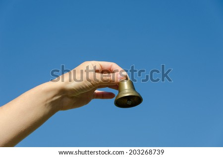 female hand hold small brass old jingle  on blue sky background  - stock photo