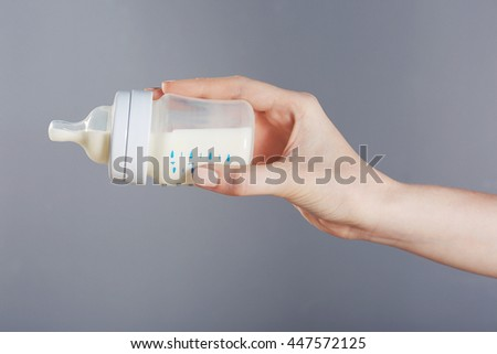 Female hand holding a baby bottle of milk on color background