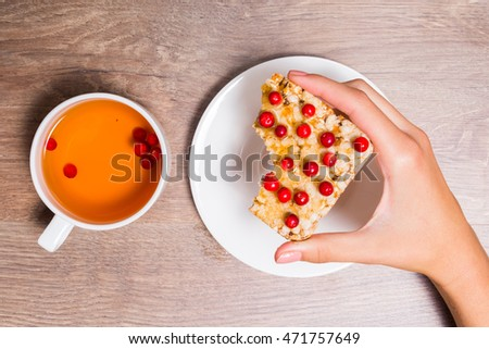 Female hand holding a bitten of sandwich of crispy bread, honey and cranberries, and cup with berry tea.
