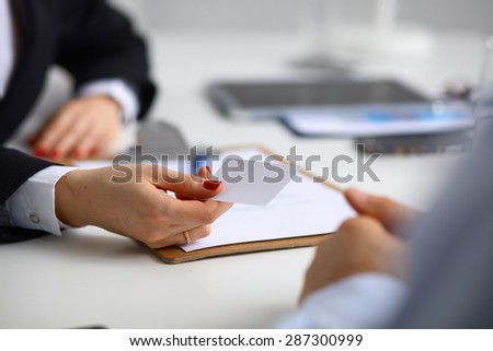 Female hand holding a blank business card .