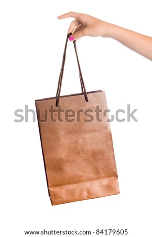 Female hand holding a brown paper shopping bag by the handle - stock photo