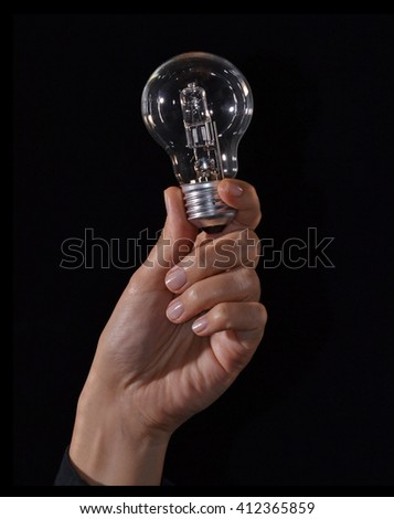 Female hand holding a bulb lamp on black background. - stock photo