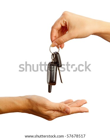 Female hand holding a car key and handing it over to another person. - stock photo