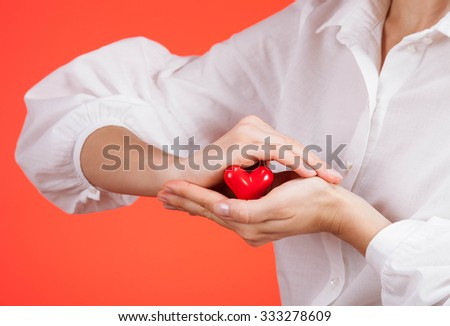 Female hand holding a ceramic heart on red background - stock photo