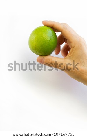 Female hand holding a fresh lime on white background - stock photo