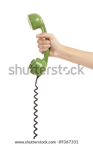 Female hand holding a green earpiece from a vintage telephone