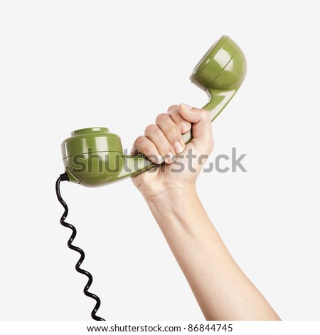 Female hand holding a green handpiece from a vintage telephone - stock photo
