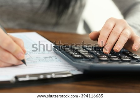 Female hand holding a pen and using calculator while filling in the individual income tax return on the wooden table, close up - stock photo