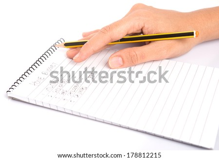 Female hand holding a pencil with list of home budget items on a notepad.