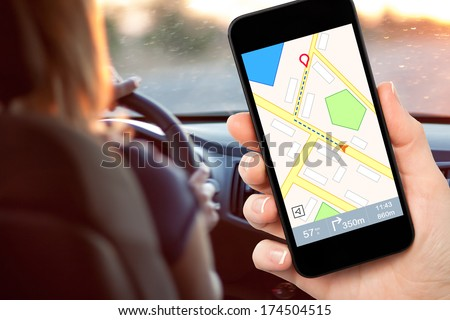 female hand holding a phone with interface navigator on a screen on a background woman driving a car - stock photo
