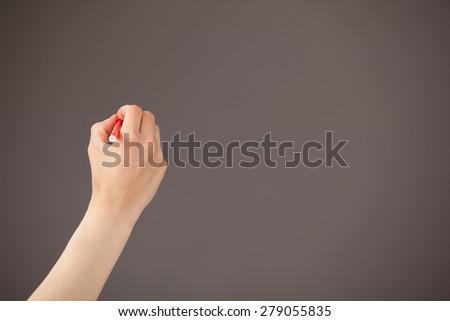 Female hand holding a red felt-tip pen on gray background - stock photo