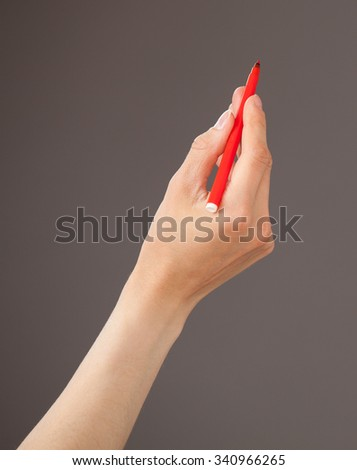 Female hand holding a red felt-tip pen on gray background