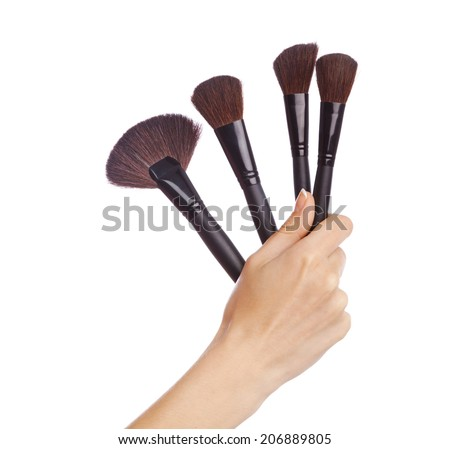 Female hand holding a set of makeup brushes, white background - stock photo