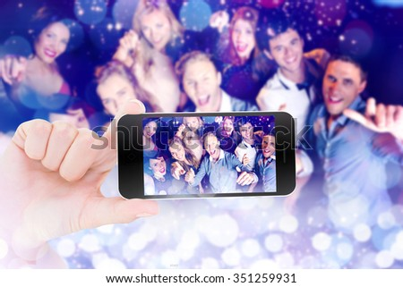 Female hand holding a smartphone against glowing background - stock photo