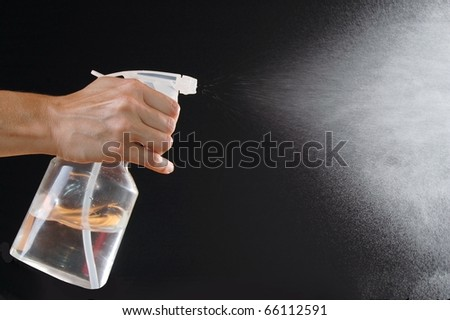 Female Hand Holding a Spray Bottle and Spraying Clear Liquid On a Black Background - stock photo