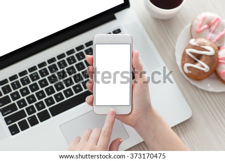 female hand holding a white phone with isolated screen on a table with a laptop - stock photo