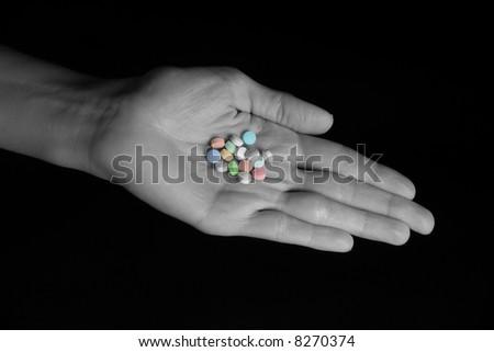 Female hand holding an assortment of generic pills - stock photo