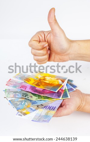 female hand holding banknotes Swiss franc and female hand showing thumbs up sign against - stock photo