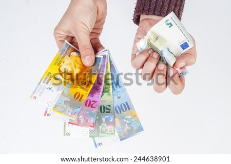 female hand holding banknotes Swiss franc and the second crumpled euro banknotes - stock photo