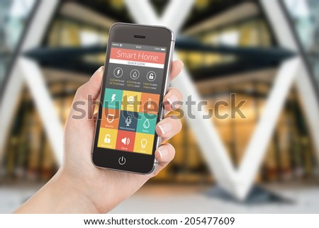 Female hand holding black mobile smart phone with smart home application on the screen. Blurred house on the background. For access to all of the controls of your house and caring of home security. - stock photo