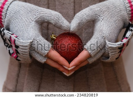 female hand holding Christmas red ball in the sign of the heart - stock photo
