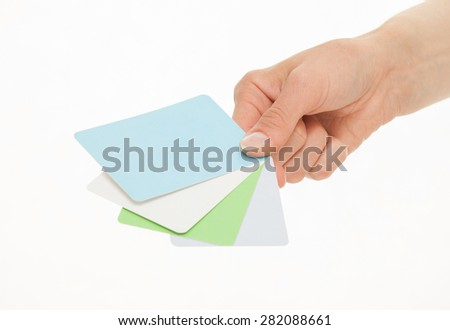 Female hand holding colorful paper cards, white background