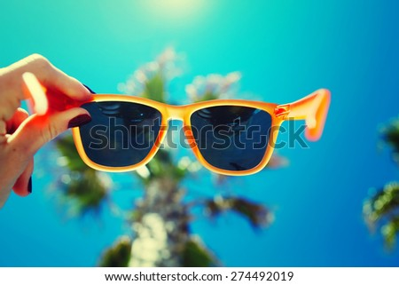 Female hand holding colorful sunglasses against palm tree and blue sunny sky, summer vacation holidays concept, first person shot, looking though glasses, filtered image - stock photo