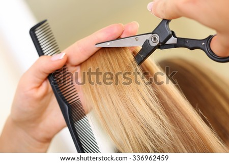 Female hand holding comb and hot thermal scissors cutting tips of long straight blonde hair lock closeup. Hairdresser salon, barber shop, perfect look, modern technique, new hairdo concept - stock photo