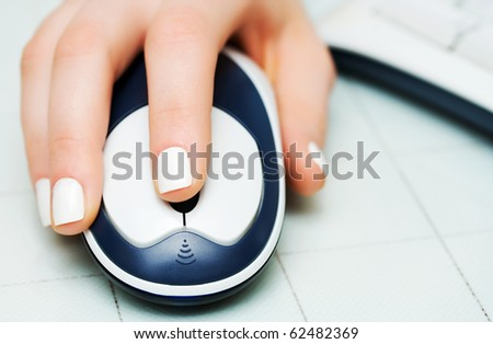 Female hand holding computer mouse. - stock photo