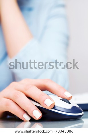 Female hand holding computer mouse - stock photo