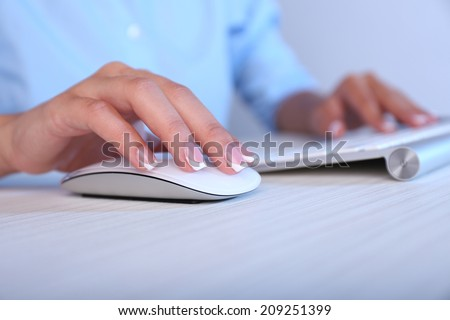 Female hand holding computer mouse, close-up - stock photo