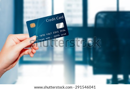 female  hand holding credit card against business office background - stock photo