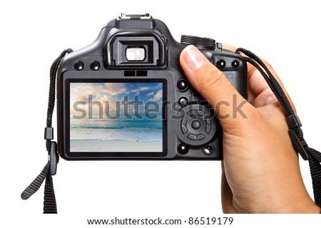 Female hand holding DSLR camera isolated on white - stock photo